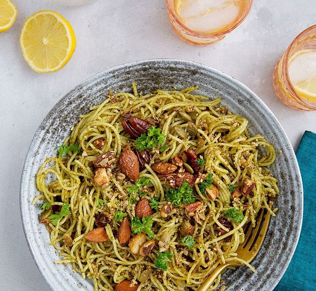 Bowl of pasta topped with herbs and nuts