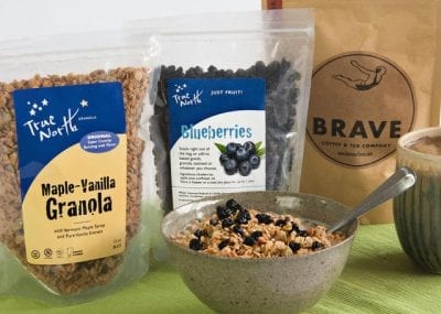 Bags of granola, dried blueberries and coffee are propped up behind a bowl of granola with blueberries.
