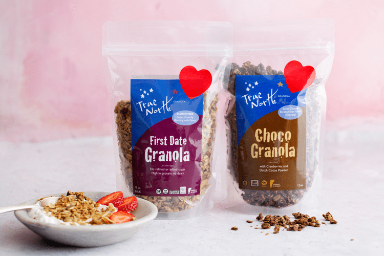 First Date Granola and Choco Granola with heart stickers on the front against a pink background.